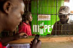 An Mpesa Agent with a User in Kenya